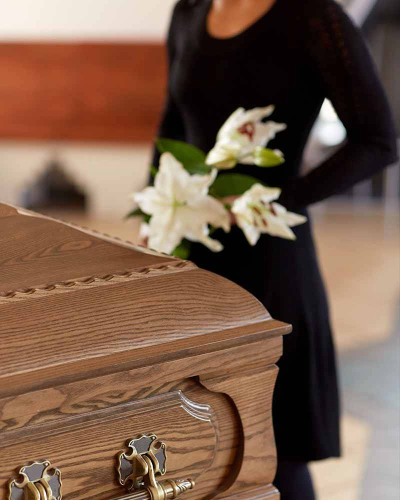 a woman stood by coffin at a funeral service