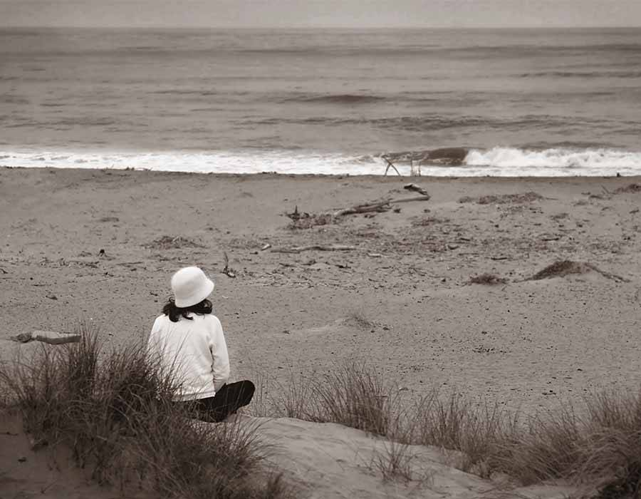sad lady on beach thinking about what to do after her husband died